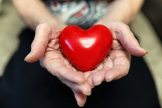 elder woman holding heart shape in a hands